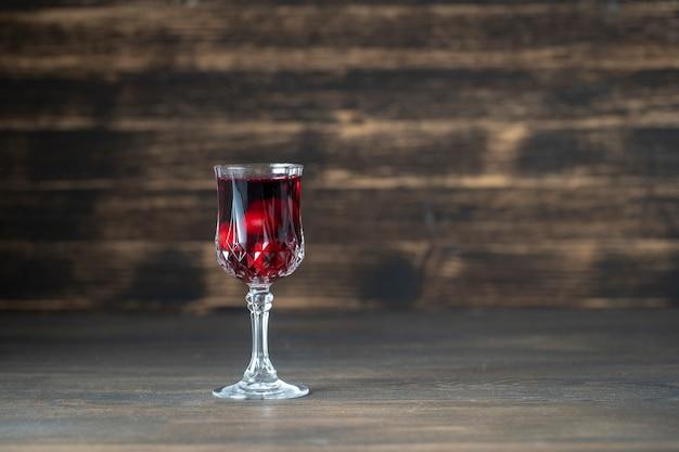 Selbst gemachte tinktur der roten kirsche in einem weinkristallglas auf hölzernem hintergrund Premium Fotos