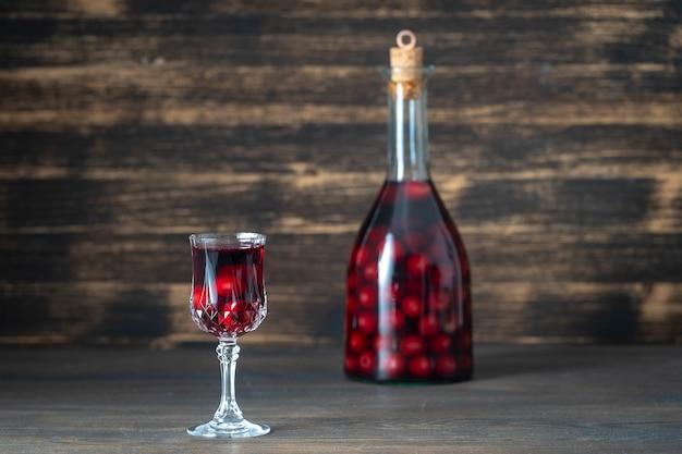 Selbst gemachte tinktur der roten kirsche in einer glasflasche und einem weinglas auf hölzernem hintergrund Premium Fotos