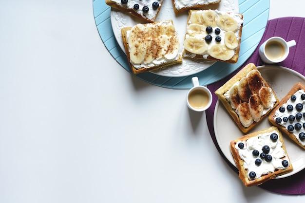 Selbst gemachte waffeln der blaubeere und der banane mit kaffee Kostenlose Fotos