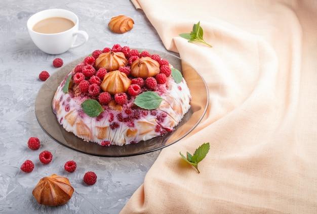 Selbst gemachter geleekuchen mit milch, keksen und himbeere auf einer grauen betonoberfläche mit tasse kaffee und orange textil, seitenansicht. Premium Fotos