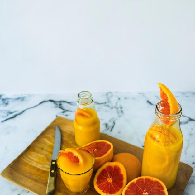 Selbst gemachter grapefruitsaft im glas und flaschen auf hackendem brett mit scharfem messer Kostenlose Fotos