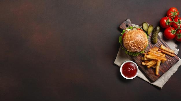 Selbst gemachter hamburger mit bestandteilrindfleisch, tomaten, kopfsalat, käse, zwiebel, gurken und pommes-frites auf schneidebrett und rostigem hintergrund Premium Fotos