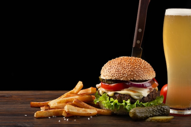 Selbst gemachter hamburger mit pommes-frites und glas bier auf holztisch. im burger steckte ein messer. Premium Fotos
