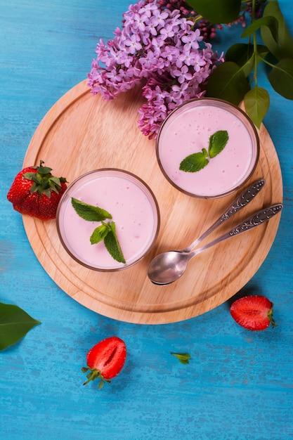 Selbst gemachter jogurt mit frischer erdbeere und minze auf blauem hölzernem hintergrund Premium Fotos