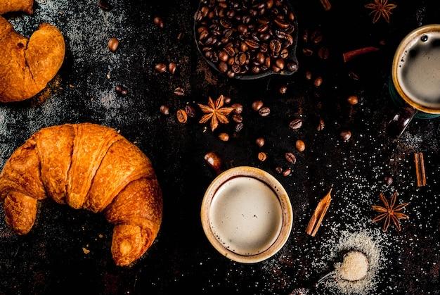 Selbst gemachter kaffee des kontinentalen frühstücks mit gewürzrohrzucker-hörnchenmarmelade auf einer schwarzen rostigen metalltabelle Premium Fotos