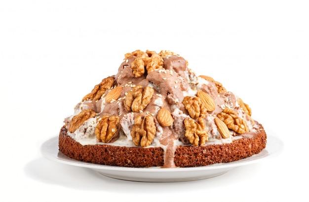 Selbst gemachter kuchen mit der milchcremekakaomandel-haselnuss lokalisiert auf weißem hintergrund Premium Fotos