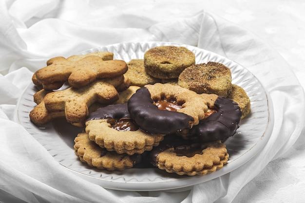 Selbst gemachter lebkuchen, zimt und schokoladenplätzchen auf weißem hintergrund von oben. flach liegen Premium Fotos