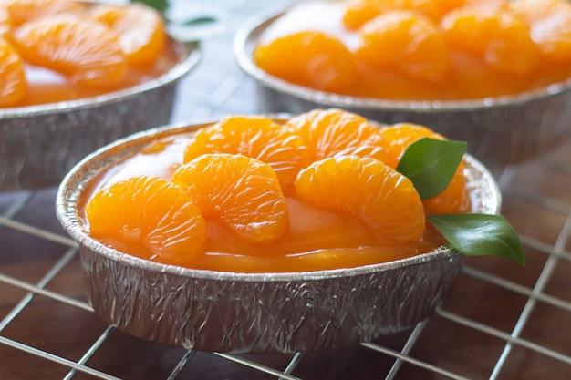 Selbst gemachter orange kuchen auf hölzerner weinlesetabelle Premium Fotos