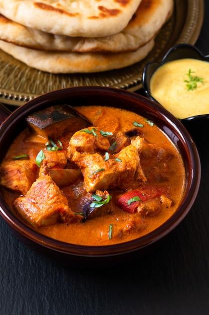 Selbst gemachter tandoori-huhn masala-curry des lebensmittelkonzeptes mit naan brot- und joghurt-dip Premium Fotos