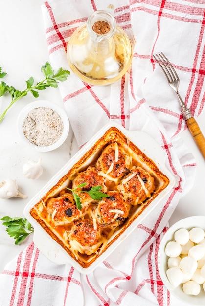 Selbst gemachtes abendessen der gesunden diät, zubereitete hühnertruthahnfleischklöschen mit soße, käse, grüns. auf einem weißen marmortisch mit gewürzen. Premium Fotos