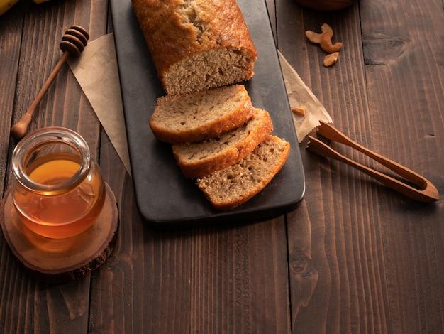 Selbst gemachtes bananenbrotpfund geschnitten mit acajounüssen und honig auf holztisch. Premium Fotos