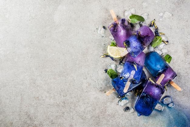 Selbst gemachtes blaues und violettes eis am stiel der natürlichen organischen sommerbonbons mit grauem konkretem hintergrund des schmetterlingserbsenblumentees Premium Fotos