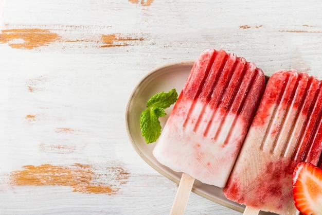 Selbst gemachtes eis am stiel des strengen vegetariers erdbeer Premium Fotos
