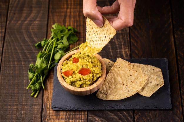 Selbst gemachtes frisches guacamole und chips essfertig. gesundes und vegetarisches essen. Premium Fotos
