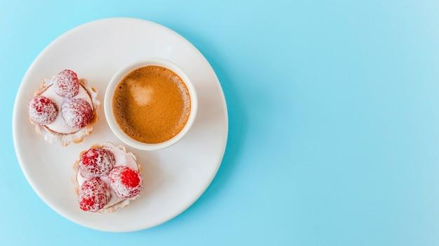 Selbst gemachtes fruchttörtchen mit himbeer- und kaffeetasse auf platte über dem blauen hintergrund Kostenlose Fotos