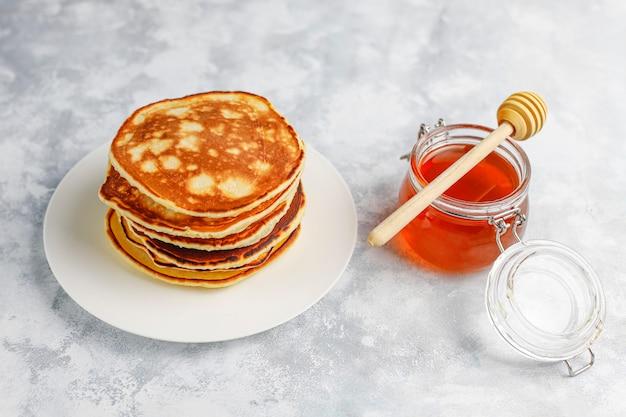Selbst gemachtes frühstück: pfannkuchen im amerikanischen stil, serviert mit birnen und honig bei einer tasse tee auf beton. draufsicht und kopie Kostenlose Fotos