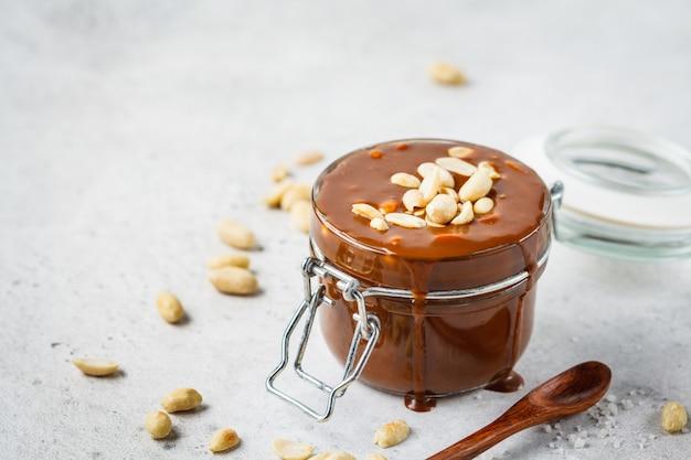 Selbst gemachtes gesalzenes karamell mit nüssen im glasgefäß, kopienraum. zutat für cake snickers. Premium Fotos