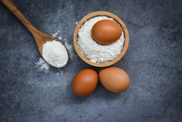 Selbst gemachtes mehl ärgert das kochen von bestandteilen auf küchentisch gebäckmehl auf hölzerner schüssel auf grauer, draufsicht Premium Fotos