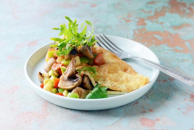 Selbst gemachtes omelett mit pilzen, gemüse und rucola auf einer platte. wunderbares gesundes frühstück nahe dem fenster mit einem tasse kaffee. Premium Fotos