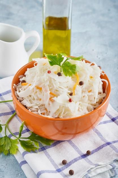 Selbst gemachtes sauerkraut mit gewürzen in einer orange schüssel. natürliche probiotika, gesunde ernährung Premium Fotos