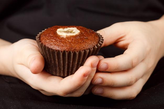 Selbst gemachtes schokoladenbananenmuffin in den händen der kinder Premium Fotos