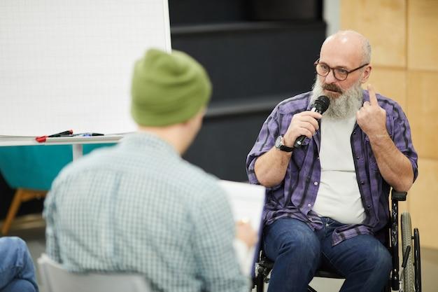 Selbstbewusster älterer mann im rollstuhl, der präsentation für studenten hält Premium Fotos