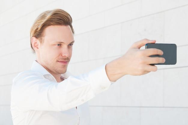 Selbstbewusster geschäftsmann, der draußen selfie foto macht Kostenlose Fotos