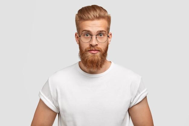 Selbstbewusster ingwer mann mit trendiger frisur, trägt eine brille, schaut direkt Kostenlose Fotos