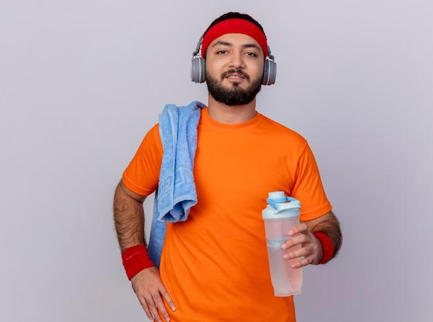 Selbstbewusster junger sportlicher mann, der stirnband und armband mit kopfhörern trägt, die hand auf hüfte setzen Kostenlose Fotos