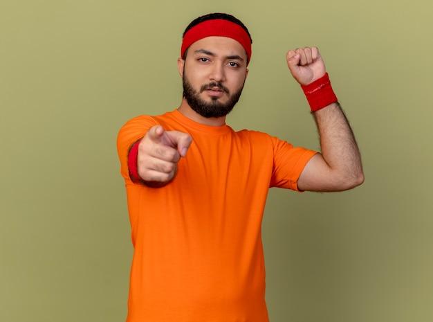 Selbstbewusster junger sportlicher mann, der stirnband und armband trägt und starke geste zeigt Kostenlose Fotos