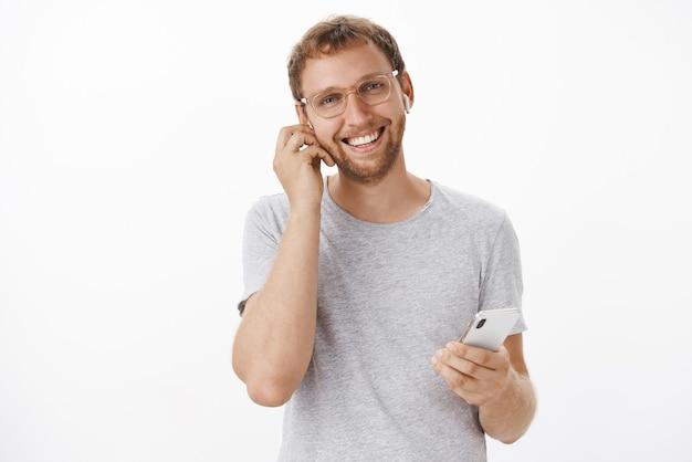Selbstbewusster und angenehmer europäischer mann, der teure angebote unterschreibt, unterhält sich mit kunden in drahtlosen kopfhörern, die ein smartphone halten, und lächelt freundlich und fröhlich, wenn er ein schönes, ruhiges gespräch führt Kostenlose Fotos