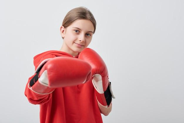 Selbstbewusstes und starkes junges mädchen in roter aktivkleidung und boxhandschuhen, die treten, während sie isoliert vor der kamera trainieren Premium Fotos