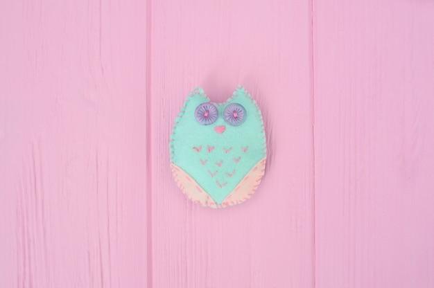 Selbstgemachte kuscheltiereule aus filz auf rosa holz Premium Fotos