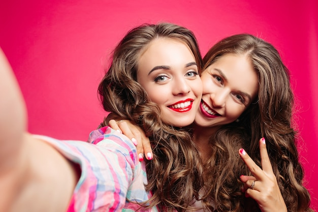 Selbstporträt von schönen brunettemädchen im rosa studio. Premium Fotos
