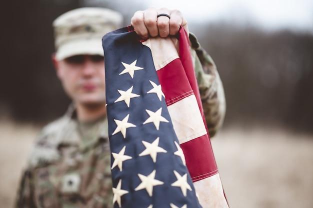 Selektive fokusaufnahme eines amerikanischen soldaten, der die amerikanische flagge nahe an der kamera hält Kostenlose Fotos