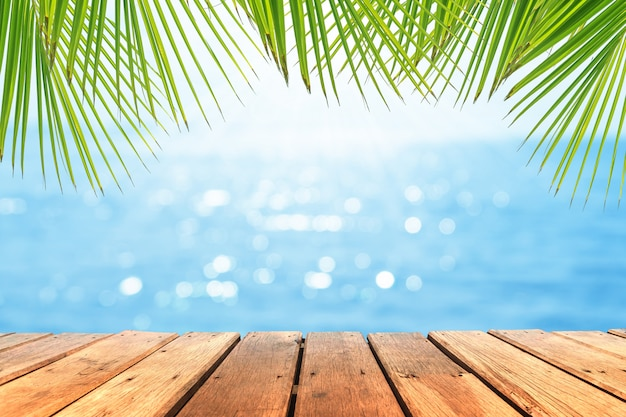 Selektiver fokus des alten holztisches mit schönem strandhintergrund für die anzeige ihres produktes. Premium Fotos