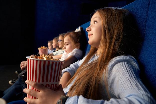 Selektiver fokus des hübschen kleinen mädchens, das popcorn-eimer hält und mit freunden in bequemen stühlen im kino sitzt. kinder, die zeichentrickfilm oder film schauen, spaß haben Kostenlose Fotos