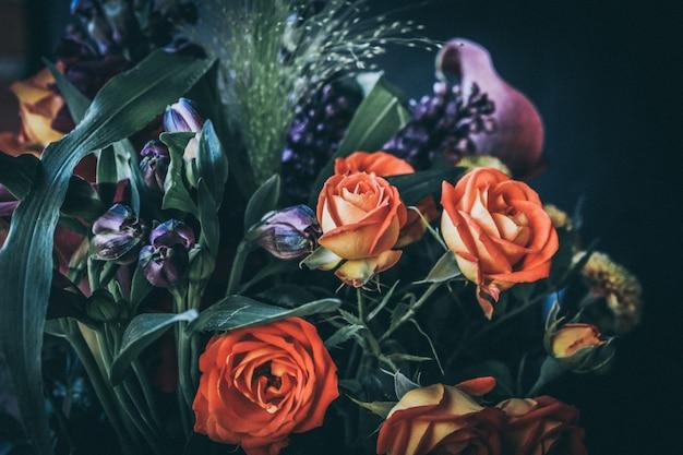 Selektiver fokus nahaufnahme schuss eines blumenstraußes mit orange rosen und lila blumen Kostenlose Fotos