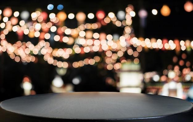 Selektiver leerer holztisch vor abstraktem unscharfem festlichem hellem hintergrund mit hellen stellen und bokeh Premium Fotos