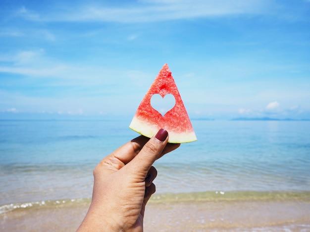 Selfie-hand, die wassermelone über sommerstrand hält Premium Fotos