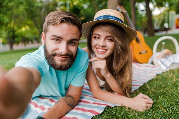 Selfie von jungen paaren auf dem picknick im park mit gitarre und obstkorb Premium Fotos