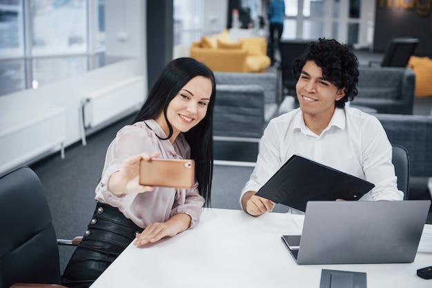 Selfie von zwei lächelnden büroangestellten in der offiziellen kleidung, die nahe silbernem laptop auf tabelle sitzt Premium Fotos