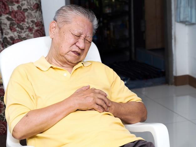 Senile asiatische männer sitzen auf einem stuhl im wohnzimmer mit herzinfarkten. Premium Fotos