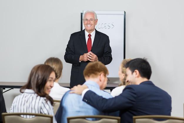 Senior Business-Mann mit einer weißen Tafel lächelnd hinter Kostenlose Fotos