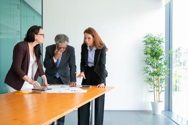 Senior chef in brillen, der statistiken beobachtet und das projekt mit partnern bespricht. inhalt erfolgreiche geschäftsleute, die mit tafeln und papieren in der nähe des tisches stehen und sprechen. geschäft und zusammenarbeit con Kostenlose Fotos