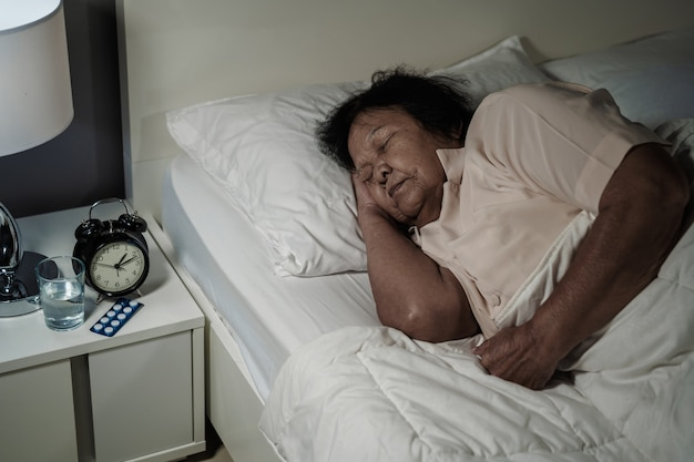 Senior frau schläft in einem bett in der nacht | Premium-Foto