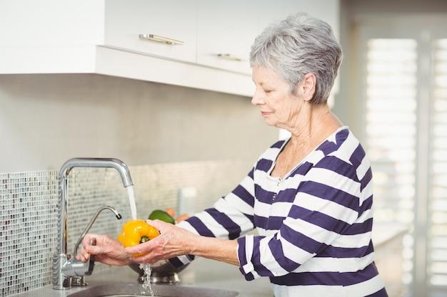 Senior frau waschen paprika Premium Fotos