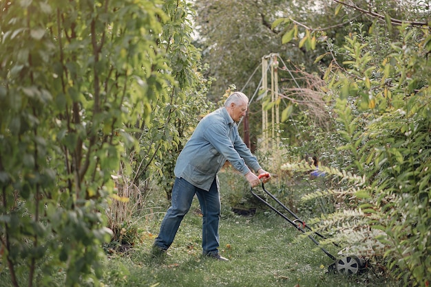 Senior mäht das gras im hof mit einem rasenmäher Kostenlose Fotos