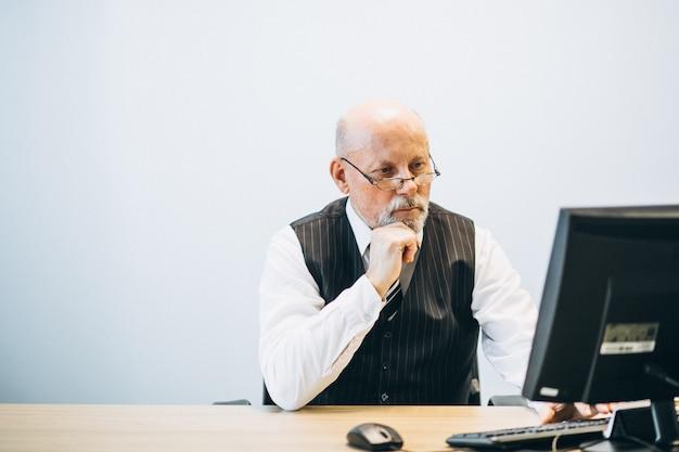 Senior manager im büro, das an einem computer arbeitet Kostenlose Fotos