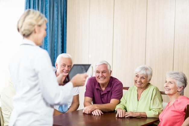 Senioren, die auf krankenschwester mit tablette hören Premium Fotos